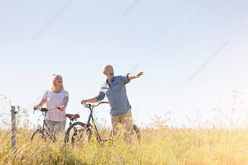 Senior couple bike riding in rural field