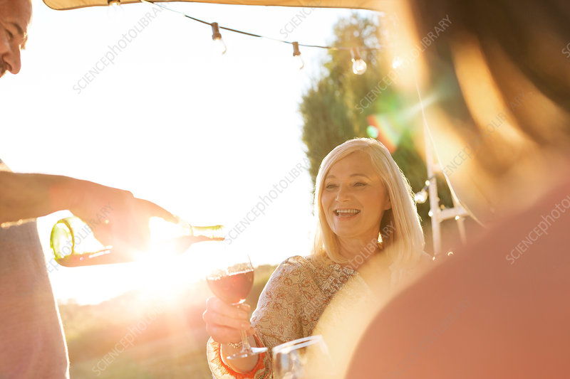Senior man pouring wine for wife on patio