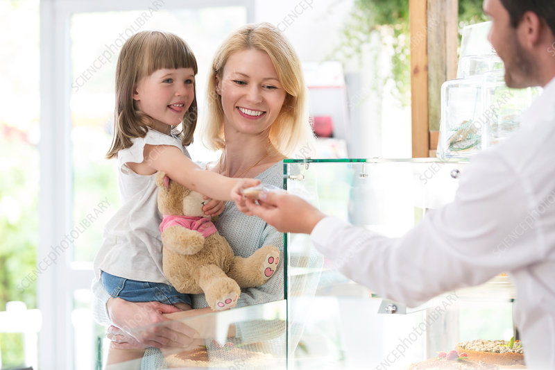 Worker giving girl cookie in bakery