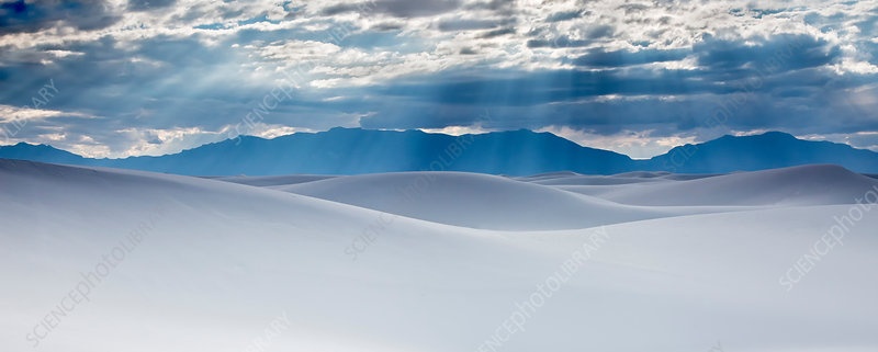 Sunbeams over tranquil white sand dunes
