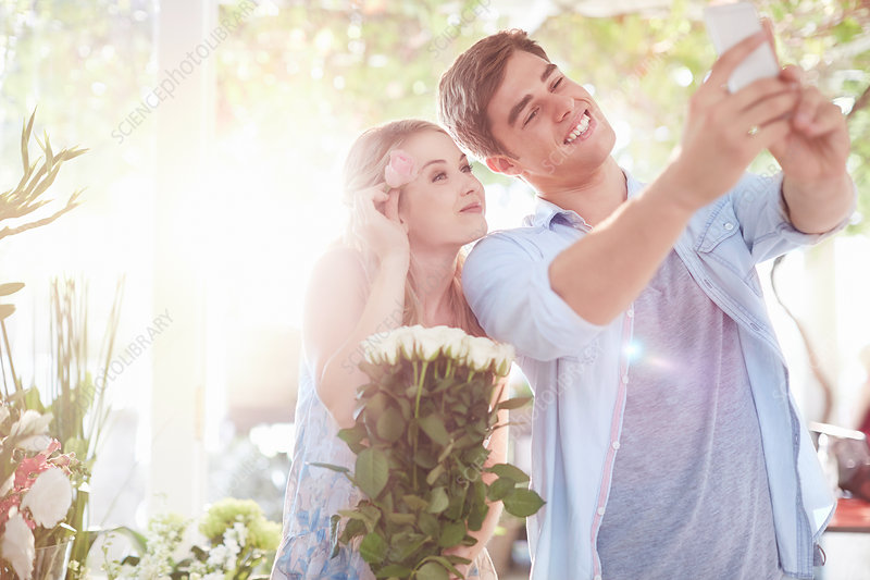 Couple taking selfie at flower shop