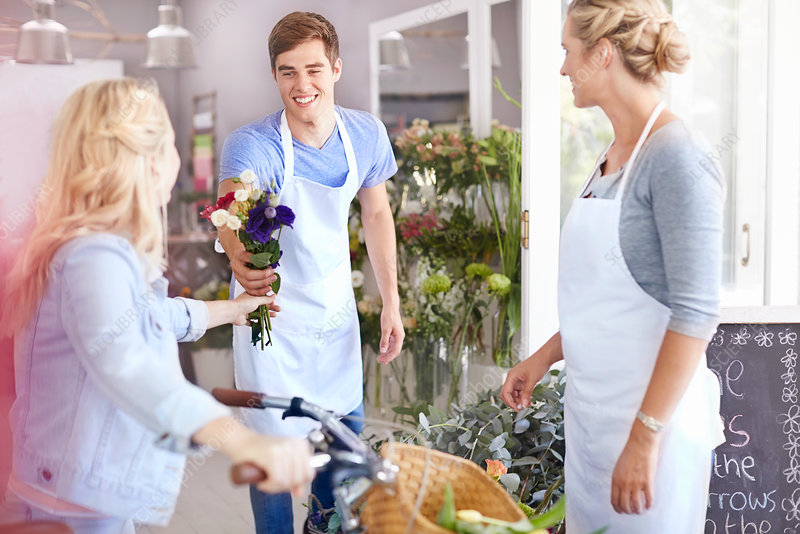 Florist giving customer bouquet
