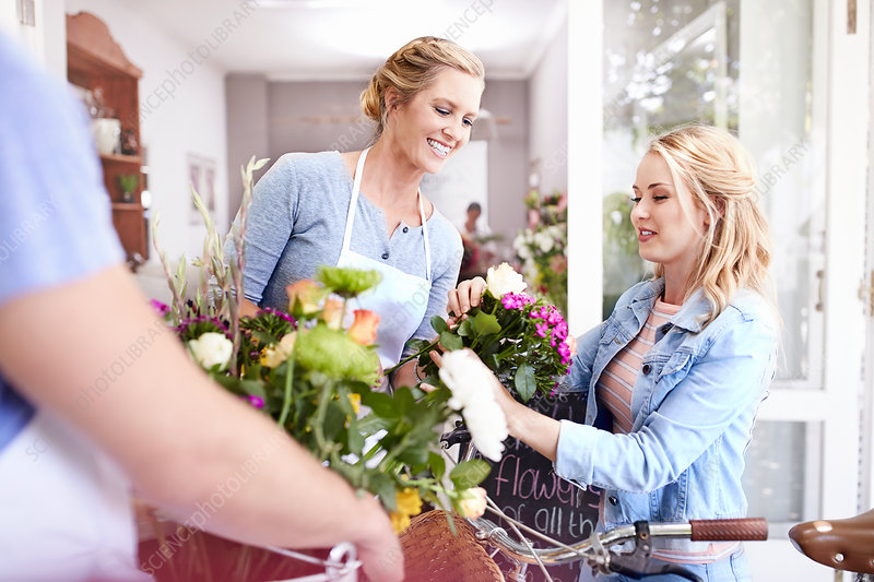 Florist helping woman pick out flowers