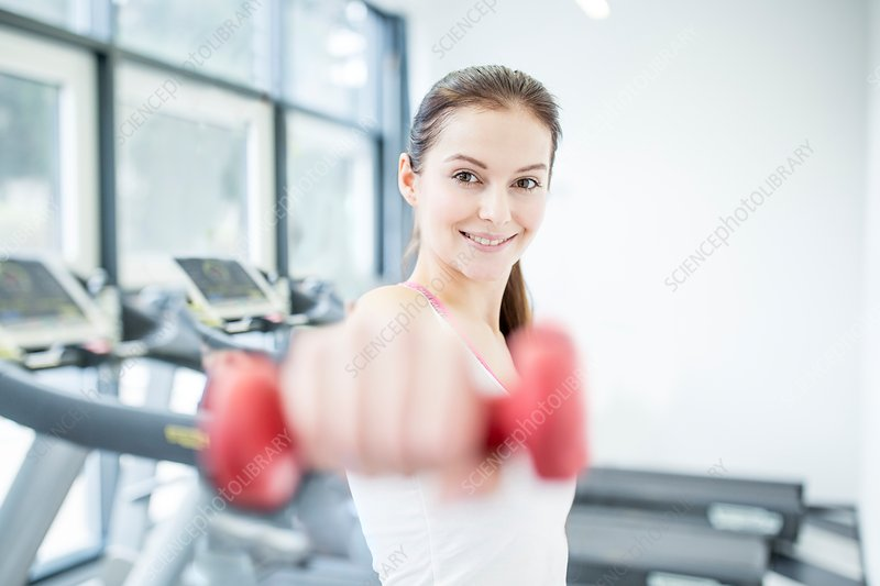 Smiling young woman holding dumbbell