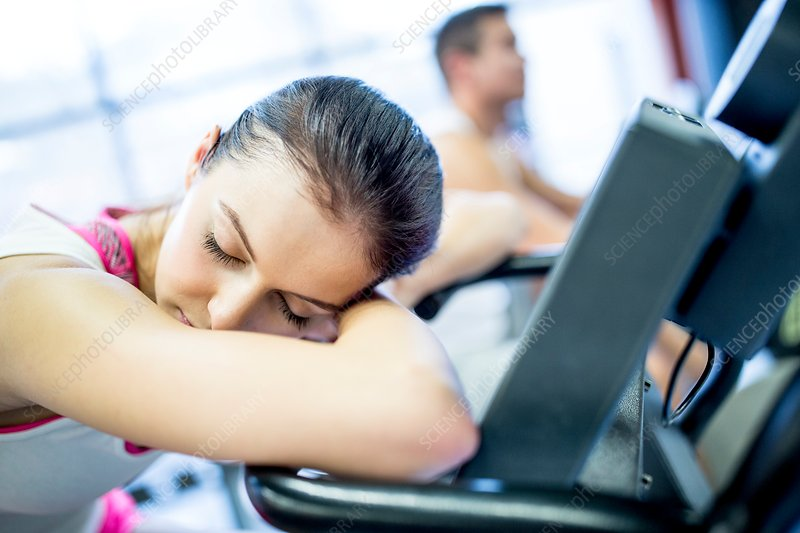 Woman resting on exercise machine