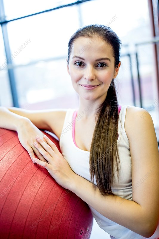 Young woman leaning on fitness ball