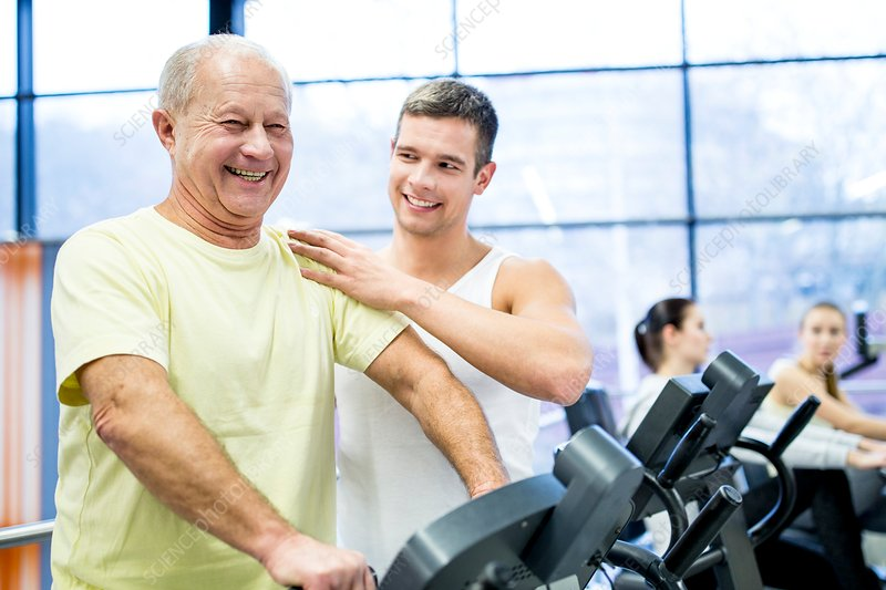 Young man assisting senior man in gym