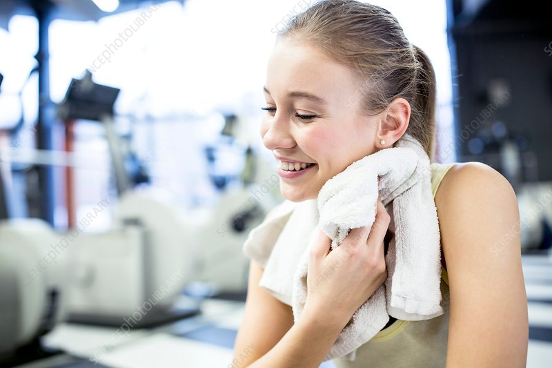 Young woman wiping her sweat with towel