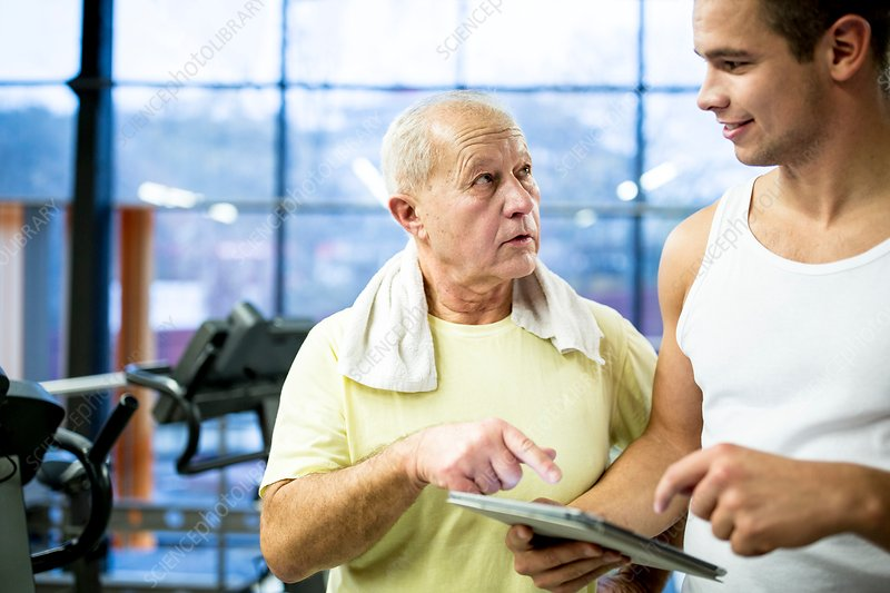 Gym trainer showing tablet to senior man
