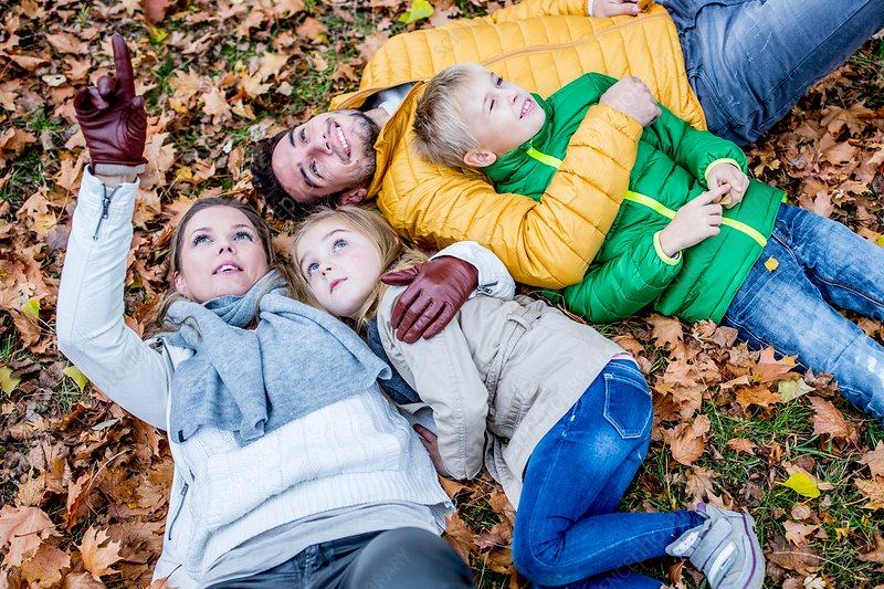 Family lying on dried leaves