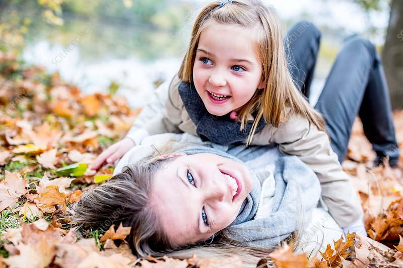 Mother and daughter lying on leaves