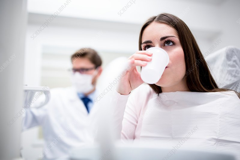 Patient rinsing in dentist's office