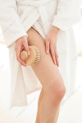 Young woman using body brush on leg