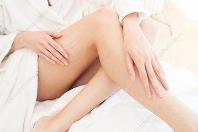 Young woman applying cream to leg