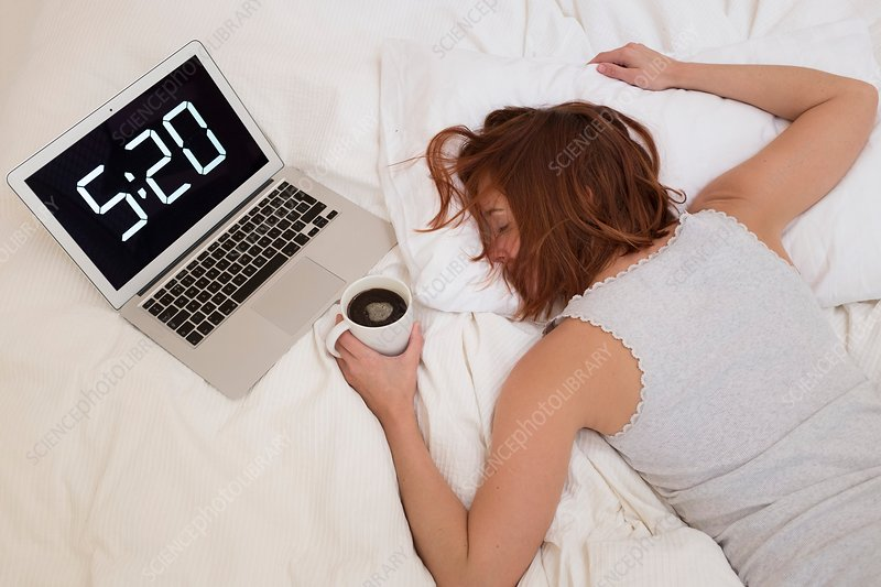 Exhausted woman in bed with laptop
