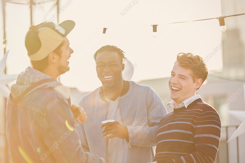 Young men laughing at rooftop party