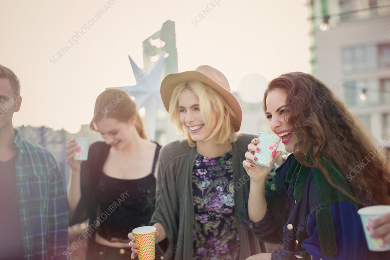 Smiling young women drinking and laughing