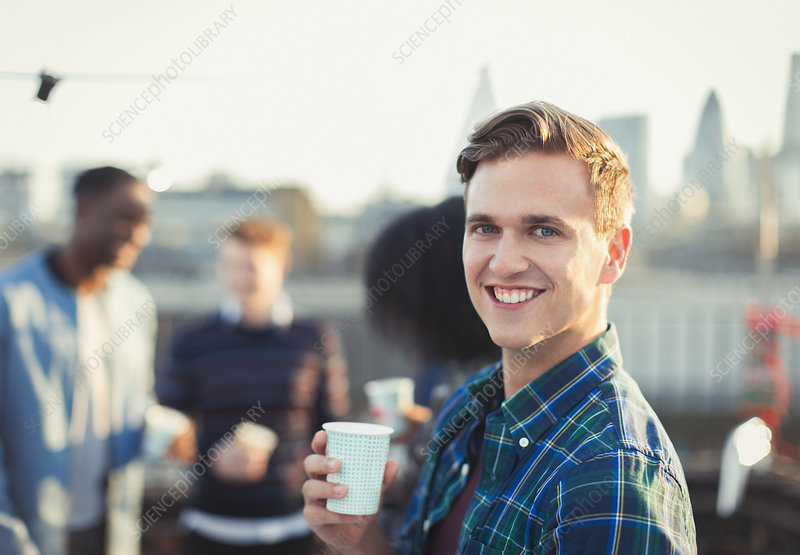 Portrait smiling young man drinking