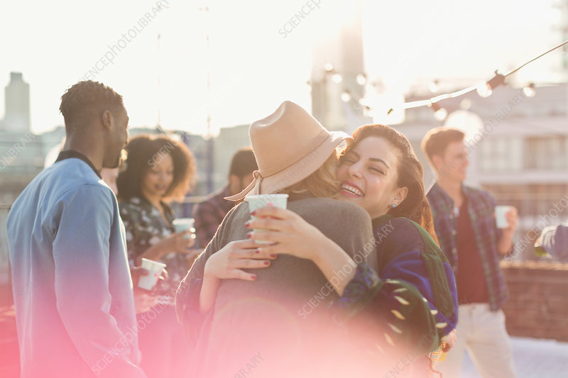 Young women hugging at rooftop party