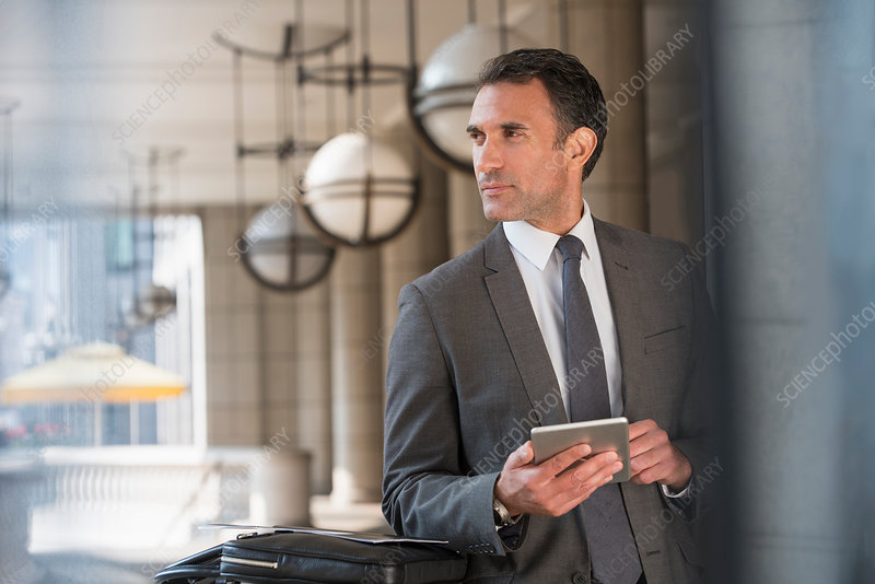 Businessman with tablet looking away