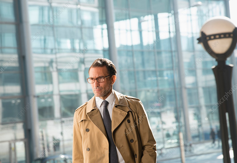 Businessman in trench coat looking away