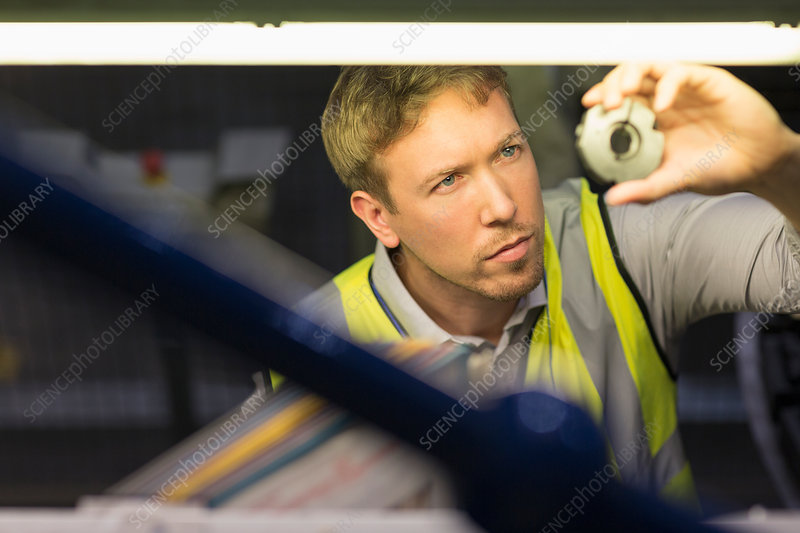 Focused worker inspecting part in factory