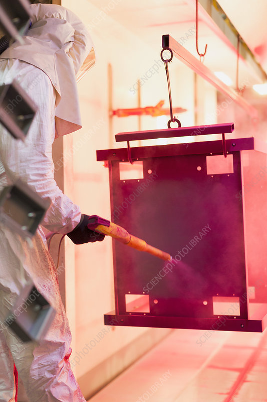 Worker painting steel red in factory