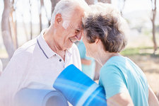 Senior couple holding yoga mats