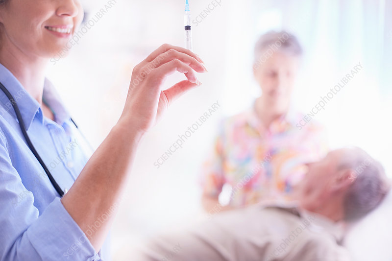 Doctor preparing syringe near senior man
