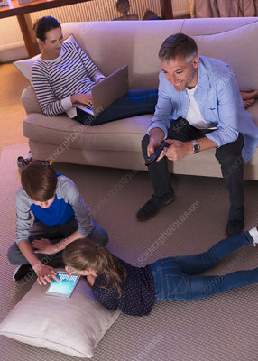 Family relaxing with technology at night
