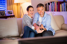 Playful couple watching TV