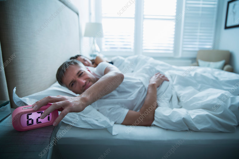 Man in bed turning off alarm clock