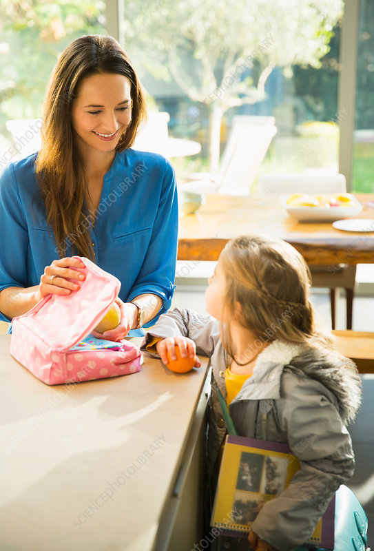Mother packing lunch for daughter