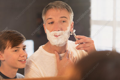 Son watching father shave face
