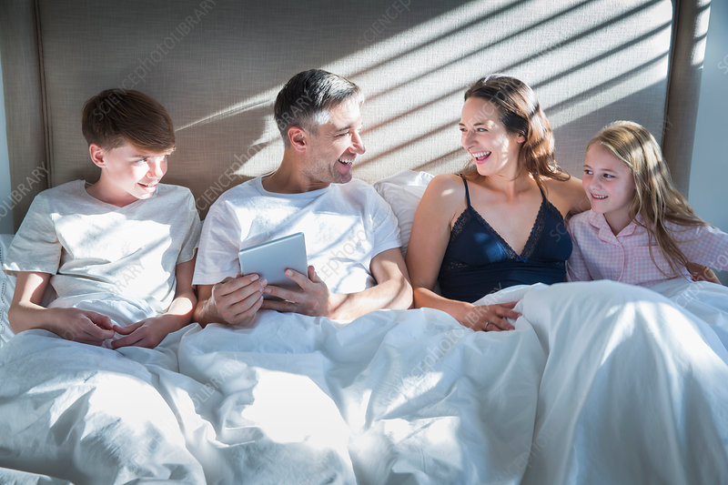 Smiling family laying in bed using tablet