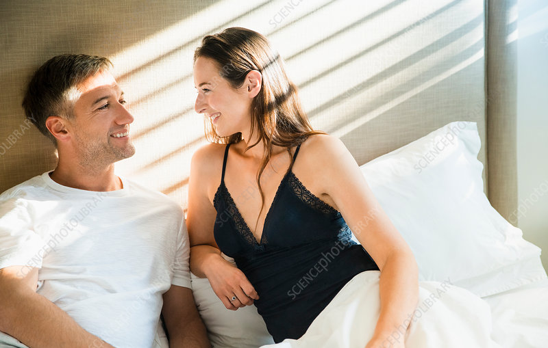 Smiling couple talking in bed
