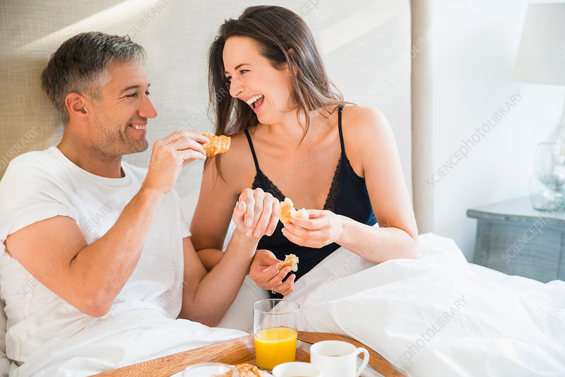 Laughing couple enjoying breakfast in bed