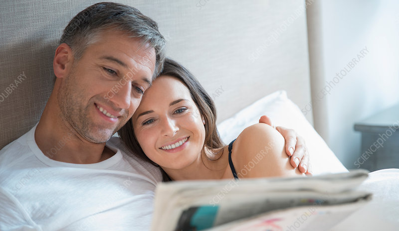 Smiling couple reading newspaper in bed