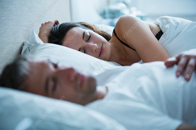 Serene couple sleeping in bed