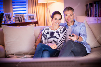 Smiling couple watching TV in living room