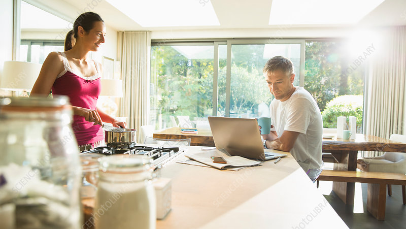 Couple cooking and working