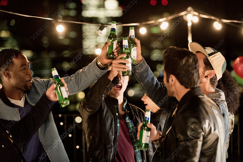 Young men toasting beer bottles