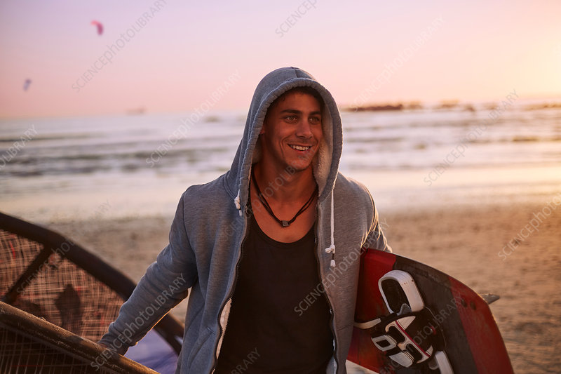 Smiling man in hoody carrying kiteboard