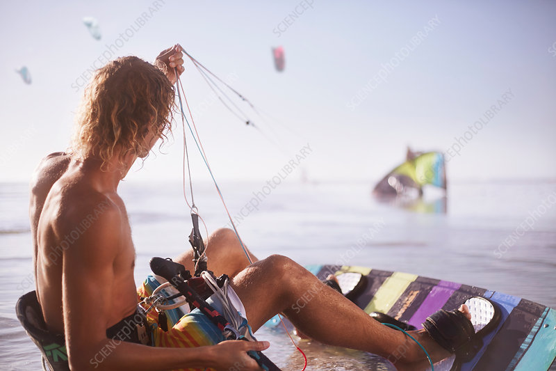 Man ready to kiteboard on beach