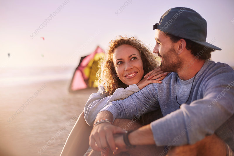 Couple sitting and talking on beach