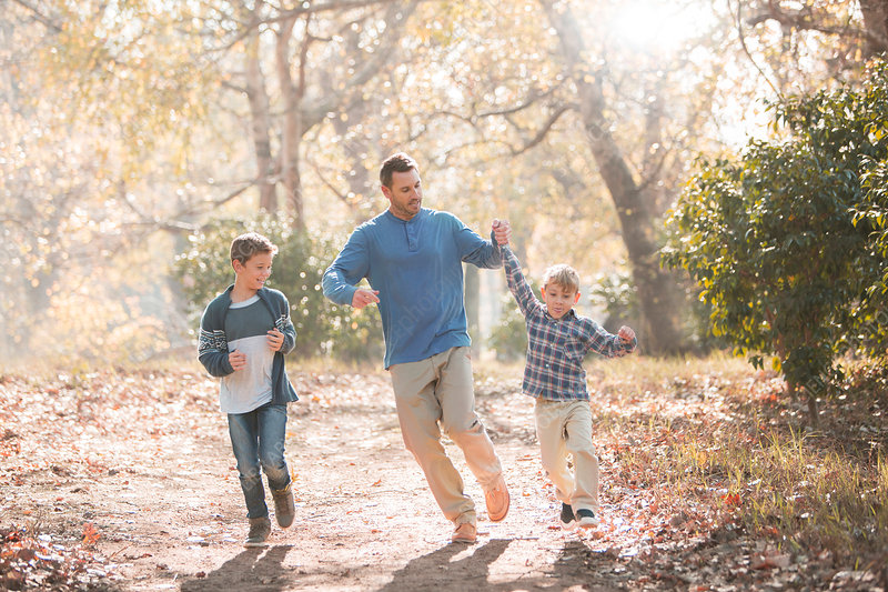 Playful father and sons running on trail