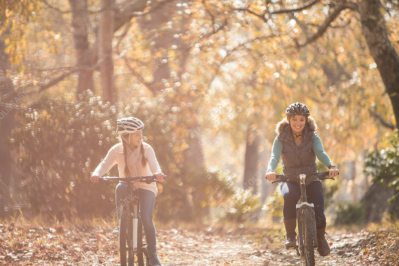 Mother and daughter bike riding on path