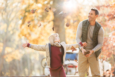 Father and son throwing autumn leaves