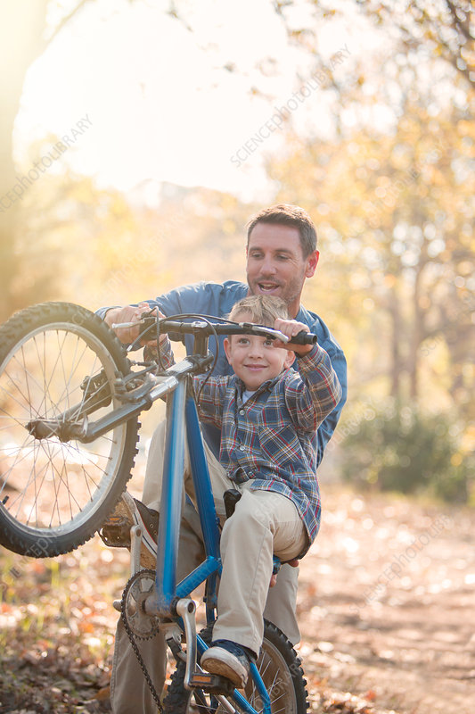 Father teaching son how to do a wheelie