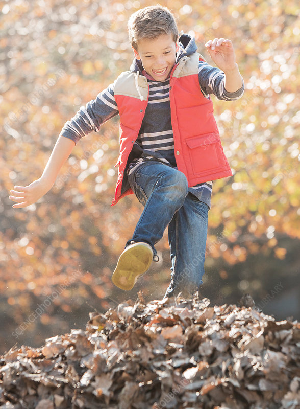 Boy jumping over pile of autumn leaves